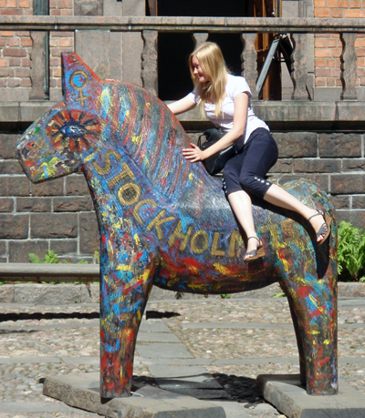 A young woman rides on a wooden horse at Stockholm City Hall